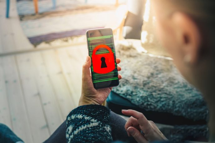 Woman holding smart phone device showing screen filled with binary code and a red padlock; Shutterstock ID 1109269646; Brand: Dark Reading; Event location or product (e.g. mag, webinar): Mag; Event / Publication Date (mm/yy): July 3; Purpose (Edit, Marketing, or Custom): Edit